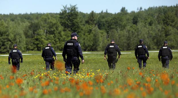 Law enforcement officers scour a field in the search for two escaped killers. (AP)