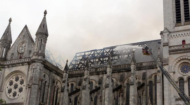 Firefighters try to put out the fire in a basilica in Nantes, western France (AP)