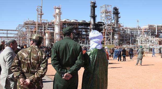 Algerian soldiers and officials stand in front of the gas plant in Ain Amenas following an attack which killed 35 hostages, including three Americans, in 2013 (AP)