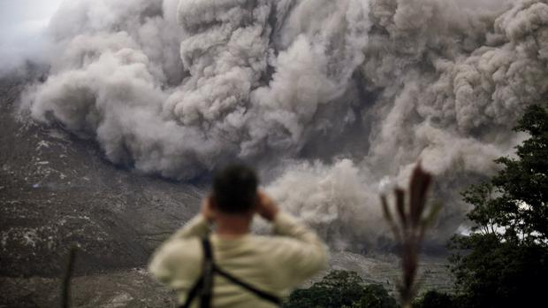 A man watches as Mount Sinabung releases pyroclastic flows in Tiga Serangkai, North Sumatra, Indonesia (AP)
