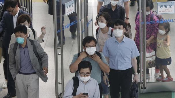 People wear masks as a precaution against Mers as they arrive at Seoul Railway Station in South Korea (AP)