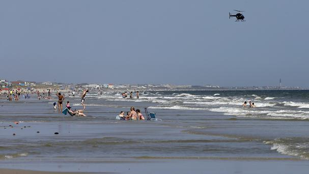 A helicopter flies close to the water as holidaymakers relax on the beach in Oak Island, North Carolina, just days after two shark attacks (AP)