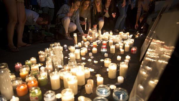 Mourners lay candles during a vigil for six Irish students in California (AP)
