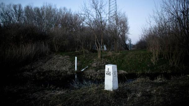 A Serbian and a Hungarian border marker next to each other in a field close to Hajdukovo. (AP)