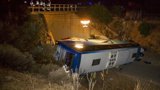 A bus lies by the side of a highway after it went off the road and rolled over into a gully in Portugal, killing three Dutch tourists. (AP)
