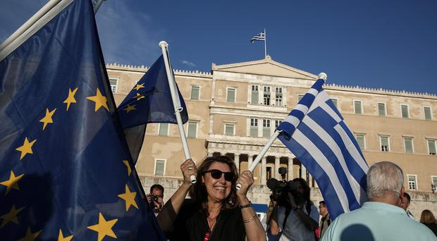 A pro-euro protester waves a Greek and a European Union flag during a rally in front of the parliament in Athens