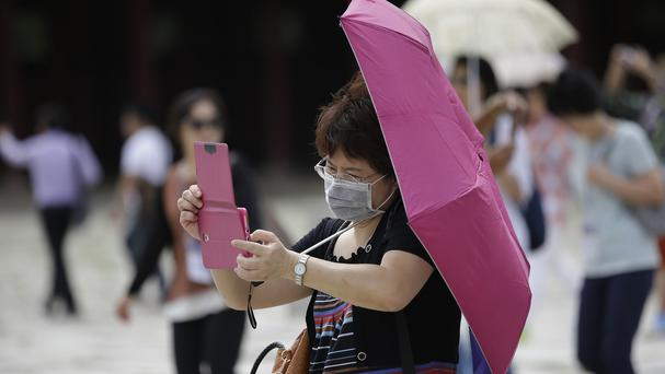 A visitor wears mask as a precaution against Mers in South Korea, where several people have died of the respiratory virus (AP)