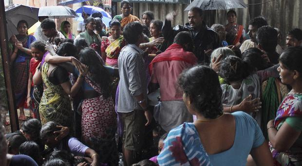 Family members of people who died after drinking tainted liquor wail at a slum area in Malad (AP)