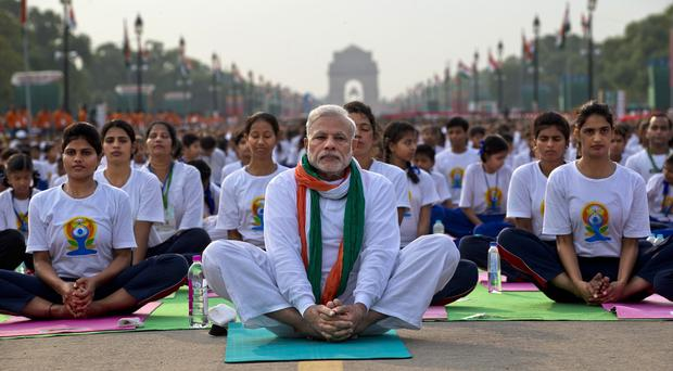 Indian prime minister Narendra Modi, centre, sits on a mat as he performs yoga along with thousands of Indians on Rajpath, in New Delhi, India (AP)