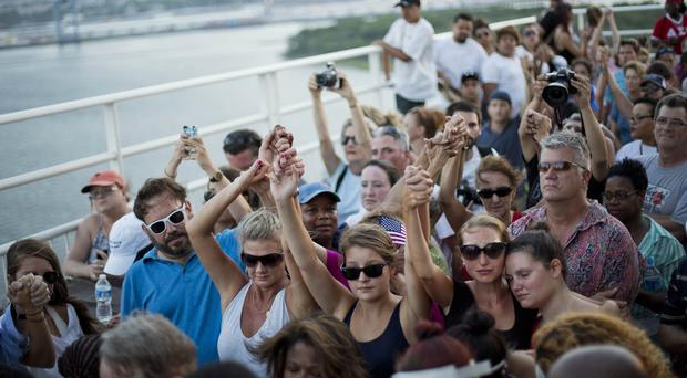 People join hands as thousands of marchers meet on Charleston's main bridge in a show of unity (AP)