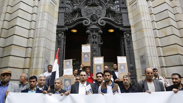 Demonstrators stand in front of the district court to support the release of journalist Ahmed Mansour in Berlin. (AP)