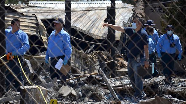 Forensics experts work among the rubble of a nursing home after it caught fire in Mexico (AP)