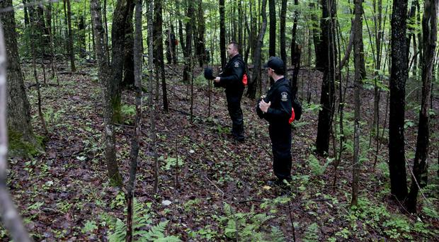 Officers walk through woods while searching for two prison escapees from Clinton Correctional Facility in Dannemora. (AP)