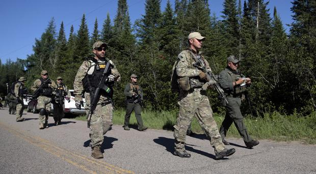 Law enforcement officers searching for two escaped prisoners in New York State