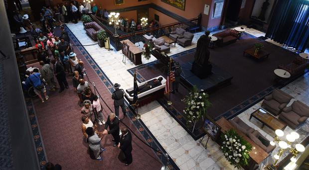 South Carolina Highway Patrol honour guard stand over Senator Clementa Pinckneys body as members of the public file past in the Statehouse (AP)