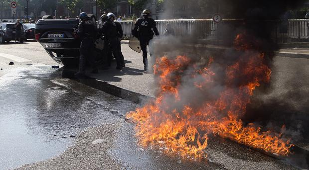 Riot police officers stand by an overturned car during as taxi drivers demonstrate in Paris (AP)