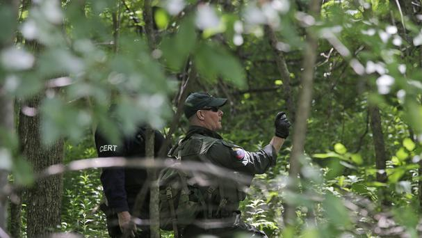 Authorities conducting a search for the convicted murderers. (AP)