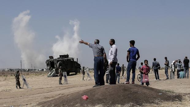 Smoke rises over the town of Kobani where 200 civilians have been killed by IS militants (AP)