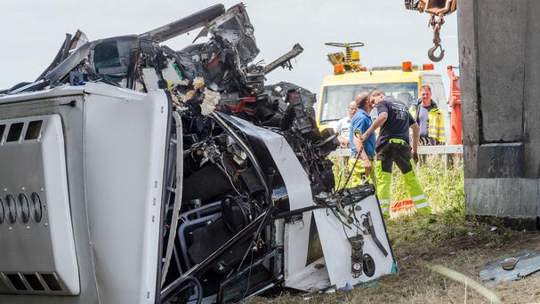 Safety workers attend to a bus which crashed on a motorway in Middlekerke, Belgium. (AP)