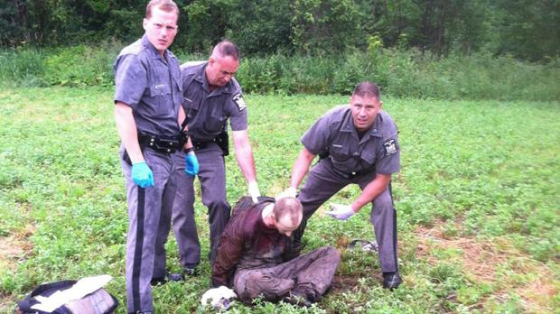 Police stand over David Sweat after he was shot and captured near the Canadian border (AP)