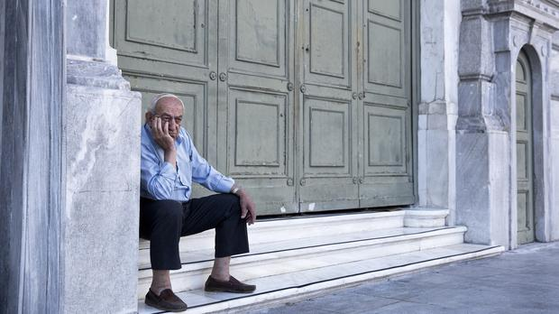 An elderly man waits to receive his pension outside the National Bank of Greece headquarters in Athens (AP)