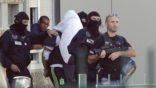 The suspect in the beheading of a businessman, Yassine Salhi, is escorted by police officers as they leave his home in Saint-Priest, outside the city of Lyon (AP)