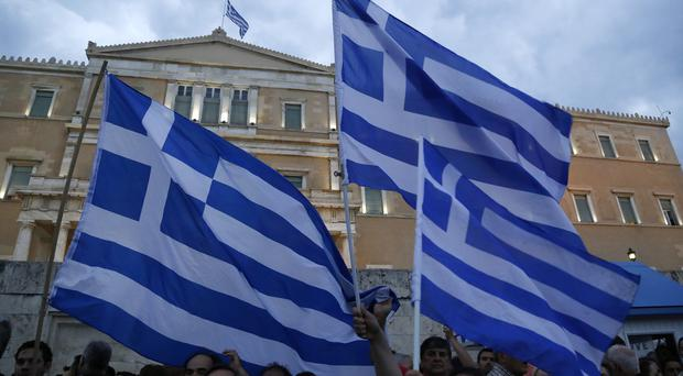 Demonstrators wave Greek flags during a rally at parliament organised by supporters of the Yes vote to the upcoming referendum (AP)