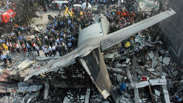 Rescuers search for victims at the site where an air force cargo plane crashed in Medan, North Sumatra (AP)
