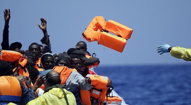 A Belgian navy sailor throws life vests to migrants in a rubber boat in the Mediterranean, off the Libyan coast (AP)