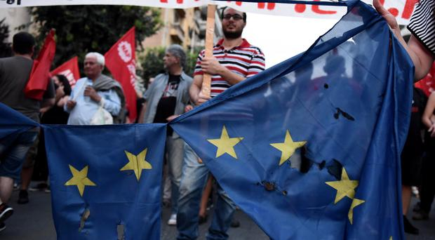 An EU flag is destroyed during a rally by referendum No vote supporters in Thessaloniki (AP)
