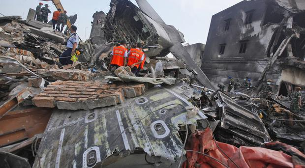Investigators inspect the wreckage of the crashed air force transport plane in Medan (AP)
