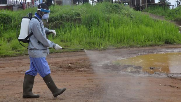 Health workers spray disinfectant on a road near the home of a 17-year old boy that died from the Ebola virus on the outskirts of Monrovia, Liberia. (AP)