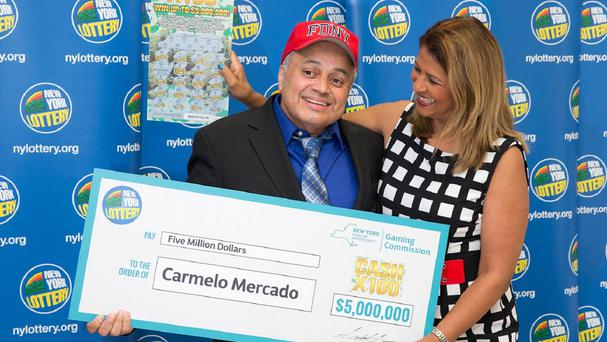 Yolanda Vega presents retired New York City firefighter Carmelo Mercado with a giant cheque (New York State Gaming Commission/AP)