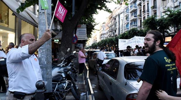 A demonstrator waves a Yes flag as a supporter of the No vote reacts in the port city of Thessaloniki (AP)