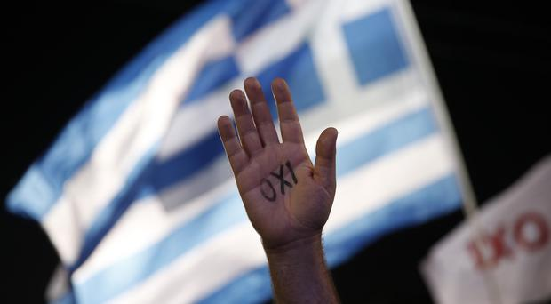 A demonstrator raises his hand reading the word No as a Greek flag waves during a rally in Athens (AP)