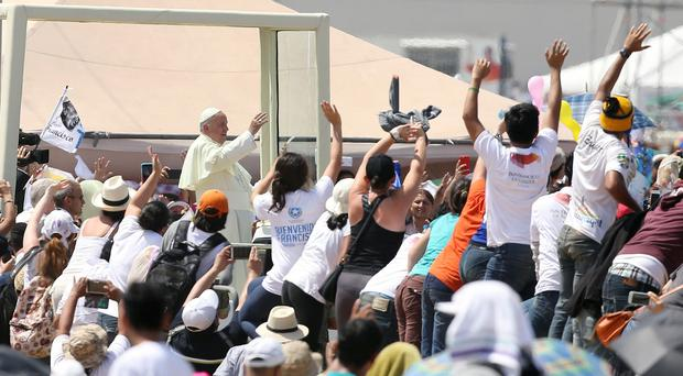 Pope Francis waves to the crowd as he arrives to celebrate Mass at Samanes Park in Guayaquil, Ecuador (AP)