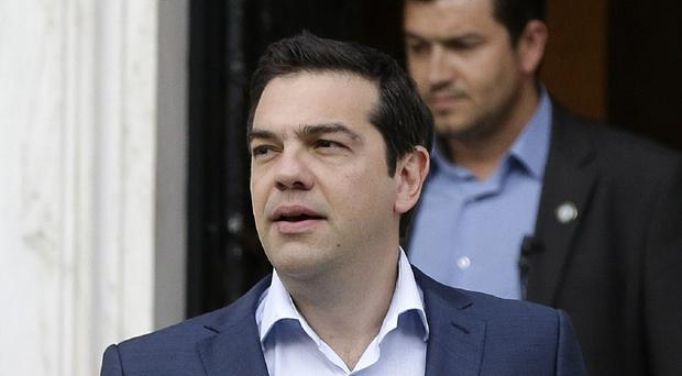 Greece's prime minister Alexis Tsipras leaves Maximos Mansion in Athens (AP)