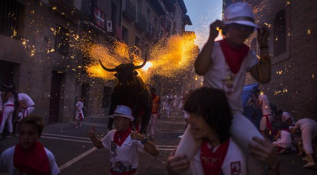 Revellers in a fake bull run on the eve of Tuesday's opening day of the San Fermin fiesta in Pamplona (AP)