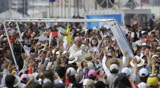 Pope Francis rides through the crowd in his popemobile as he arrives to celebrate Mass at Bicentennial Park in Quito, Ecuador (AP)