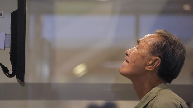 A man watches the Hong Kong share index inside a local bank (AP Photo/Vincent Yu)