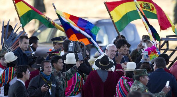 Pope Francis and Bolivia's president Evo Morales walk together upon the pontiff's arrival at El Alto International airport (AP)