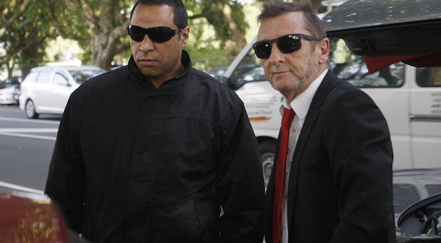 AC/DC drummer Phil Rudd, right, arrives at a court in Tauranga, New Zealand (AP)
