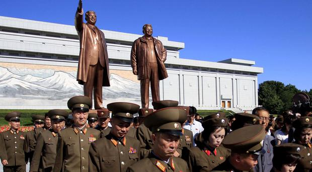 Military personnel pay their respects to Kim Il Sung at a statue of their former leader and his son, Kim Jong Il, at Mansu Hill (AP)