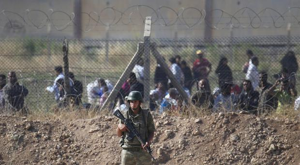 A Turkish army soldier guards the border area with Syria as in the background Syrian refugees wait in order to cross into Turkey (AP Photo/Lefteris Pitarakis, file)