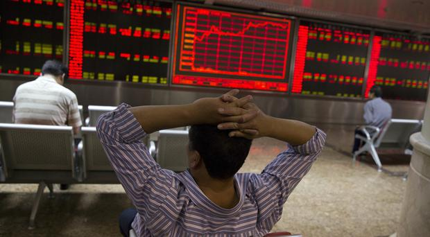 Chinese investors monitor stock prices in Beijing (AP)