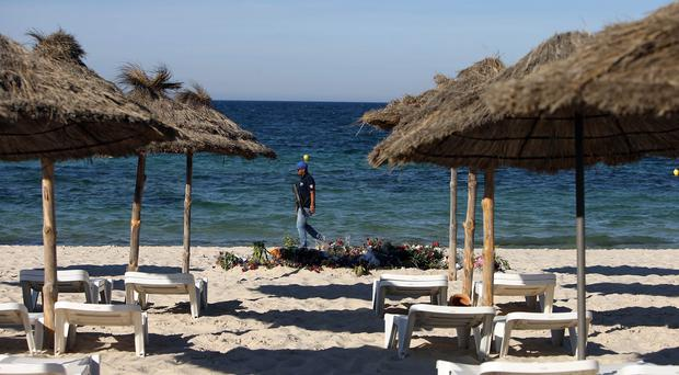 An armed policeman patrols on a beach at Sousse, Tunisia