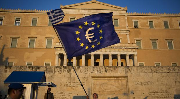 A demonstrator waves a European Union flag in front of the Greek Parliament during a rally in Athens (AP)