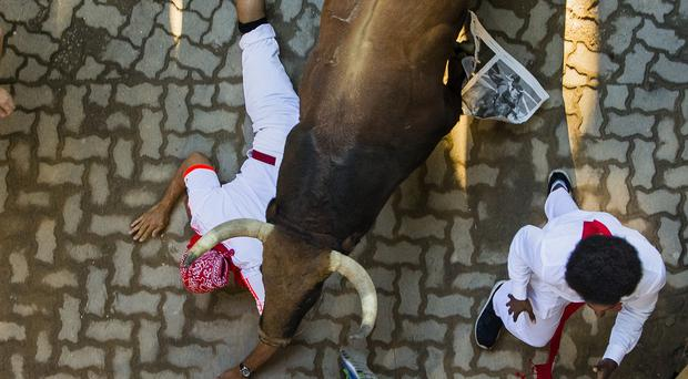 A fighting bull runs over a reveller during the running of the bulls in Pamplona. (AP)