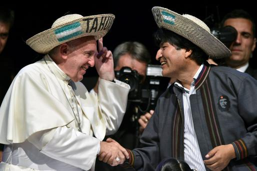 A sombrero-wearing Pope Francis is greeted by Bolivian President Evo Morales