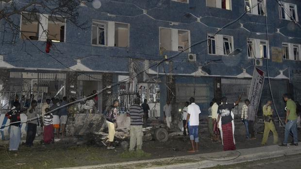Somali security forces and civilians gather outside the Weheliye hotel after it was attacked by militants (AP)